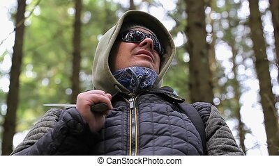 Hiker with machete staring at the tree tops in forest