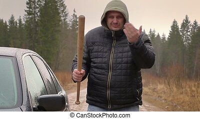 Aggressive man with a baseball bat near car in rainy day