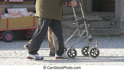elderly man is walking with a walking frame - 4K native...