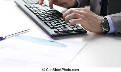 close up of male hands with charts and keyboard - people,...
