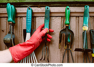 hand takes garden tools - hand in red gloves takes old...