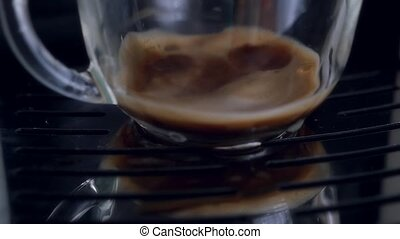 coffe dispenser with cup of coffee. Slowmotion pouring -...