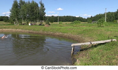 people jump in pond - young girl and man with hat jump into...