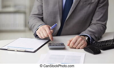 close up of businessman with papers and calculator -...