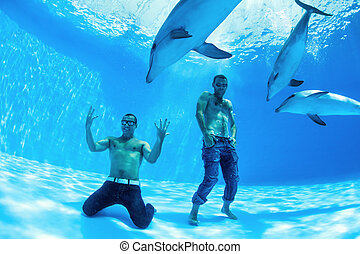 two men and three dolphin fooling around on the bottom of...