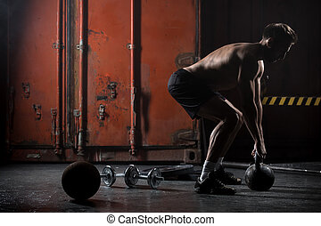 Beautiful athlete doing kettlebell swings. View from the...