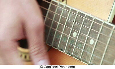 Enumerating strings - Male hand plays guitar string
