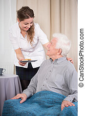 Caring nurse and older man - Young caring nurse giving the...