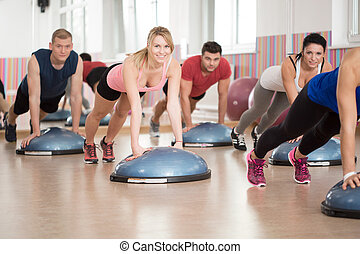 Fitness group training with bosu at the gym