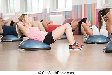 Abs exercise on bosu ball - Fitness group doing abs exercise...