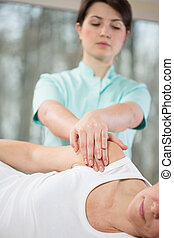Therapy of shoulder - Patient lying on the couch during...
