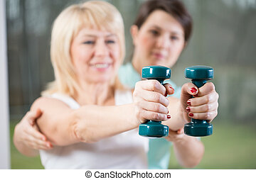 Female training with dumbbells assisted by physiotherapist