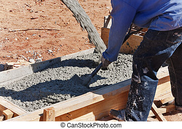 construction worker mixing concrete in the foundation with a...