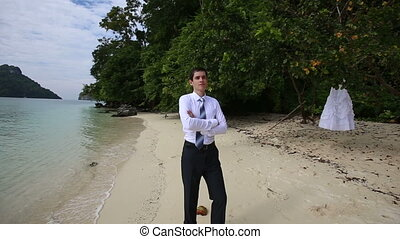 groom in black trousers stands crossing arms on beach -...