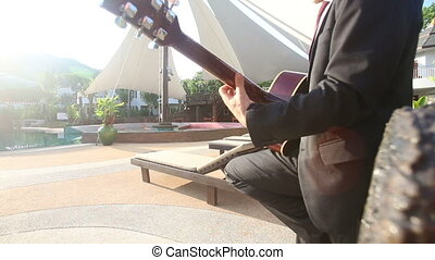 blonde man in black suit and sunglasses plays guitar