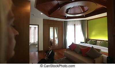 girl looks at man playing guitar going round room - girl...