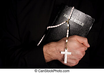 Holy Bible and Rosary - A priest holding The Holy Bible and...