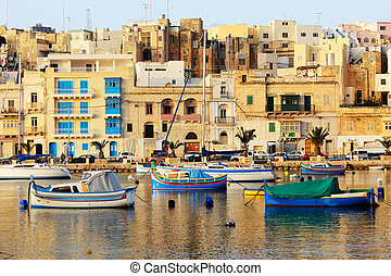 The view on traditional Maltese boats in sunset, Kalkara,...