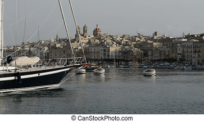 The cruise Luzzu boat swimms by and yacht marina, Birgu,...