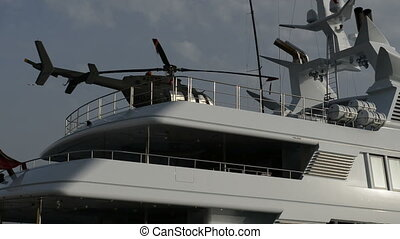 The modern yacht with helicopter on top in yacht marina,...