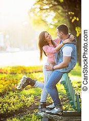 Active people - Young couple on roller skates in the park