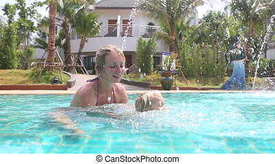 little girl learns to swim and splashes in pool