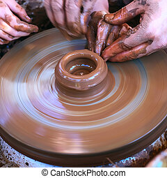 Hands working on pottery wheel - Potters hands guiding...