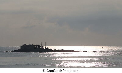 view of house on small cliff island in sea at dawn