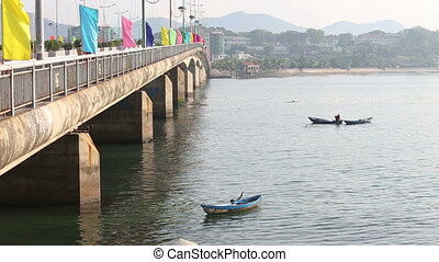 fisherman in boat fishes with landing-net near bridge -...