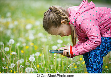 Little girl photographing with her smartphone - Little...