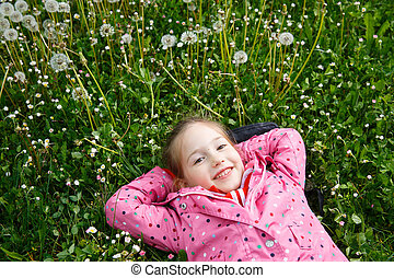 Girl lying in grass, surrounded by dandelion - Beautiful...