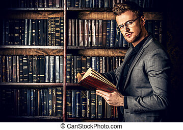 lawyer - Handsome well-dressed man stands by bookshelves in...