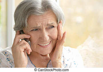 elderly woman calling on phone at home