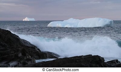 Iceberg with waves breaking on rocks