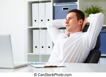 Handsome young businessman resting in office