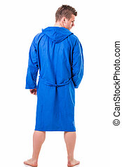 Handsome young man wearing blue bathrobe, isolated on white...