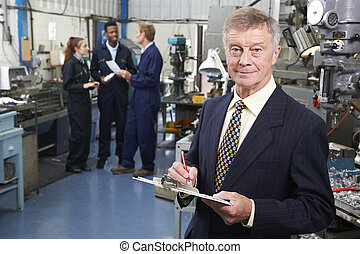 Owner Of Engineering Factory With Staff In Background