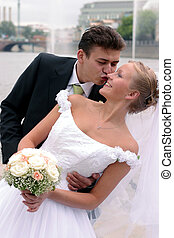 Newlywed couple kissing - Young newlywed couple kissing...