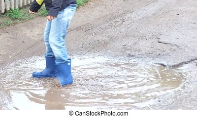 Happy boy playing in puddle after the rain