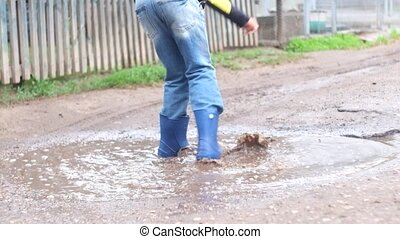 Boy in blue jeans playing in puddle after the rain.
