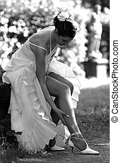 Bride adjusting stockings - Smiling bride sat outdoors...