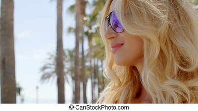 Blond Woman Wearing Sunglasses Looking at View - Head and...