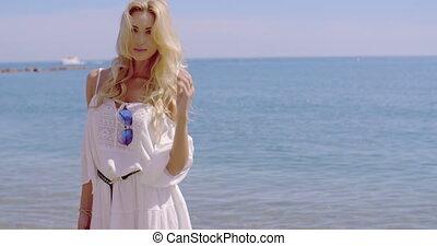 Blond Woman in White Sun Dress Standing on Beach - Waist Up...