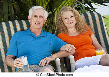 A senior man and woman couple enjoying drinks together on vacation after retirement