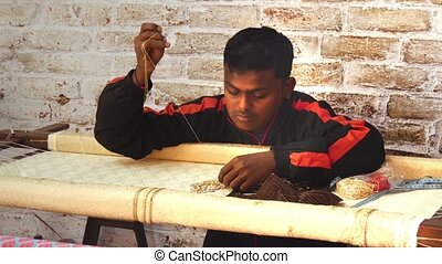 embroiderer at work - portrait of an Asian artisan in his...