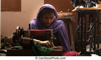 Asian seamstress at work - portrait of an Asian artisan in...