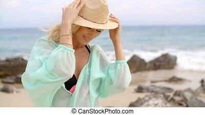 Portrait of Blond Woman Wearing Sun Hat on Beach - Waist Up...