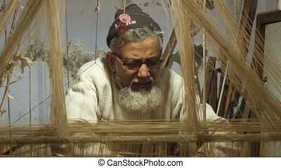 Asian weaver at work - portrait of an Asian artisan in his...