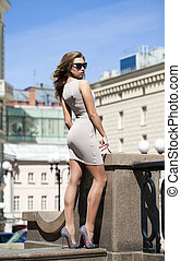 Young beautiful woman in beige short dress posing outdoors...
