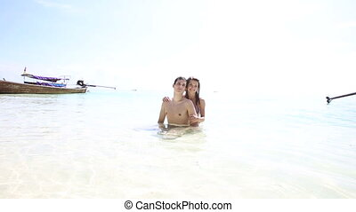 young girl and guy hugging stand in azure sea water